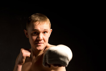 Determined young boxer throwing a punch