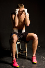 Boxer sitting on a stool with his fists raised