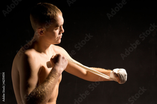 Young boxer putting on his bandages