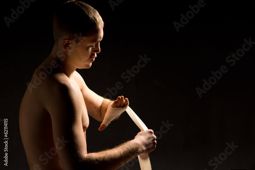 Young pugilist applying a bandage to his hand