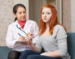 doctor examining teenager girl with thermometer