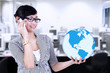 Businesswoman calling and holding a globe