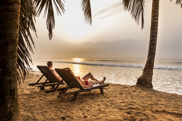 Couple on the sunbeds on the tropical beach