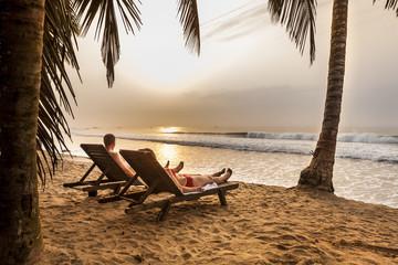 Couple on the sunbeds on the tropical beach