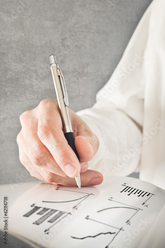 Businessman drawing chart and other infographics in note pad