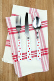 Kitchen cutlery on napkin on wooden table