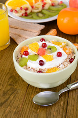 Delicious oatmeal with fruit in bowl on table close-up