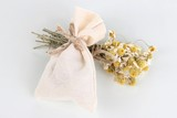 Textile sachet pouch with dried flowers isolated on white
