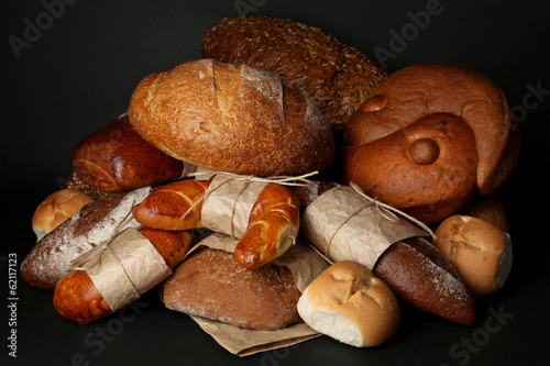 Different types of bread on black background, close-up