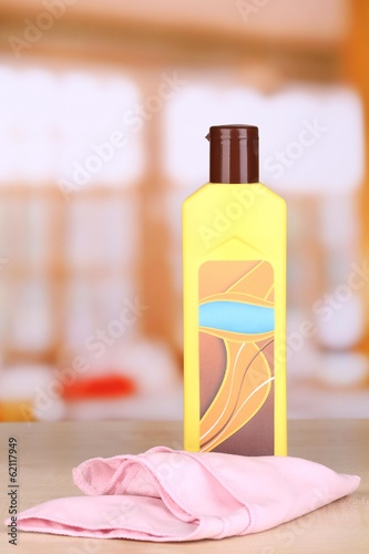 Bottle of furniture polish on wooden table