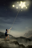 Young woman pulling bright stars