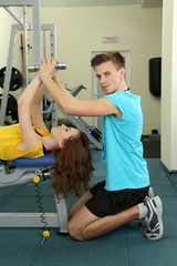 Young trainer and woman engaged with dumbbells in gym