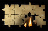 Burning wooden puzzle on dark background.