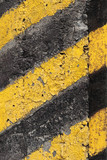 Black and yellow striped caution pattern on old concrete wall