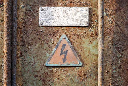 High voltage triangle sign mounted on grunge metal wall