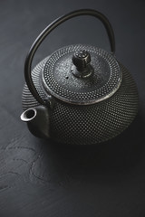Close-up of a black cast-iron asian teapot, vertical shot