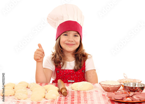 happy little girl cook with dough and thumb up