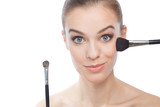 Young beautiful woman with makeup brushes