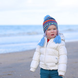 Cute toddler girl standing on the beach on a sunny spring day