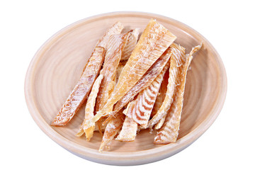 Slices of stockfish on plate made of wood, insulation image.