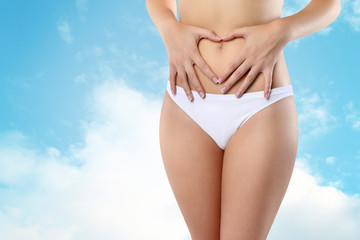 Woman's hands on stomach on sky background wellness concept