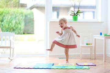 Happy blonde toddler girl having fun dancing indoors