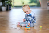 Cute little baby girl play with plastic bricks sitting indoors o