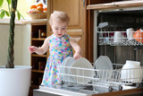 Toddler girl taking plates out of dish washing machine