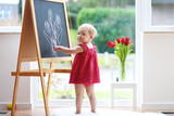 Toddler girl drawing with chalk on black board next to window