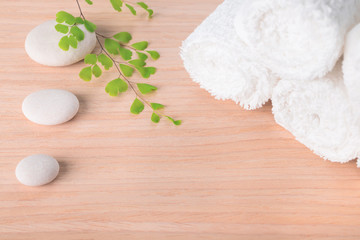 Spa still life with stone, green  branch  and white towel on woo