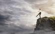 Leinwandbild Motiv Risk, young businesswoman walking over the edge of the cliff
