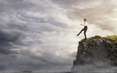 Risk, young businesswoman walking over the edge of the cliff