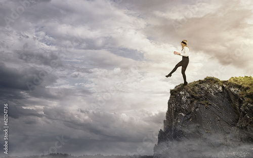 Leinwanddruck Bild Risk, young businesswoman walking over the edge of the cliff