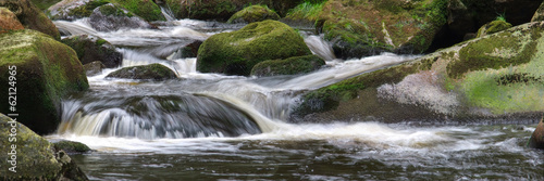 Wide nature photo of small waterfalls with forest background