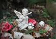 Engel sitzt auf winterlichem Gesteck auf einem Grab
