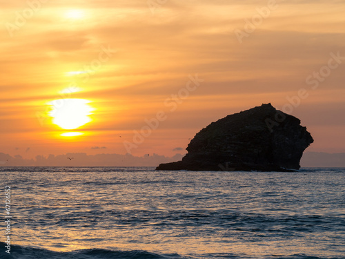 Sunset over the sea and Gull Rock, Portreath, Cornwall England.