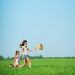 Young happy girls running witch baskets at green wheat field