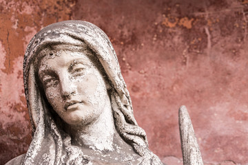 portrait of a weathered sculpture of maria with red background