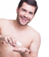 Young happy handsome man pours lotion.