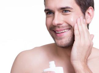 Young happy man applying cream.