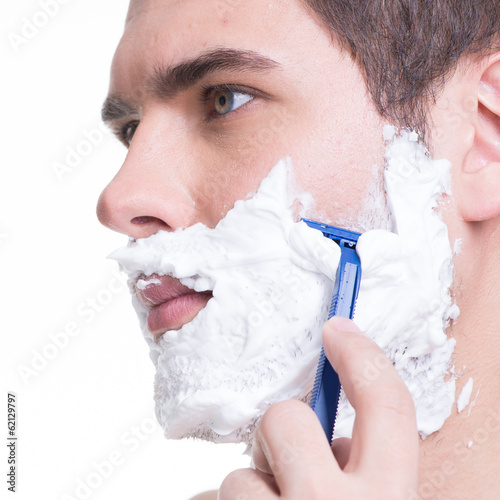 young man shaving the  beard with the razor
