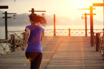back of fitness woman runner running at wooden pier