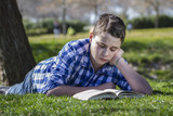 Young boy reading a book in the woods with shallow depth of fiel