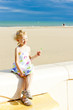 little girl with a lollipop on the beach at sea