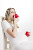 portrait of pregnant woman eating red apple