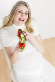 portrait of pregnant woman eating vegetable salad in red pepper