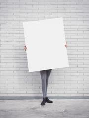 Girl holding blank poster