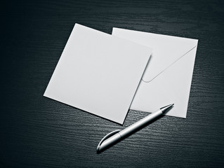 White envelope letter and white pen on black table