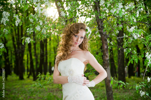 Beautiful bride in a white dress in blooming gardens