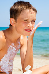 Boy applying sunscreen